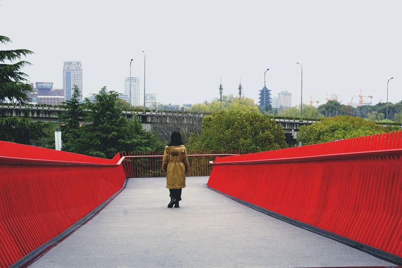 Rear view of woman walking on sidewalk in city against sky