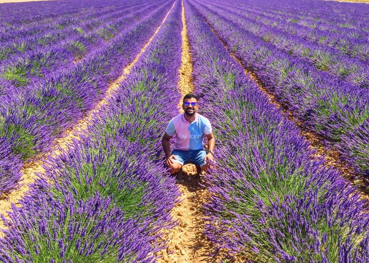 Full length of man crouching amidst lavenders in farm