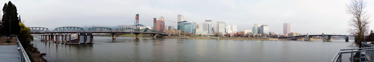 Bridge over river and buildings against sky