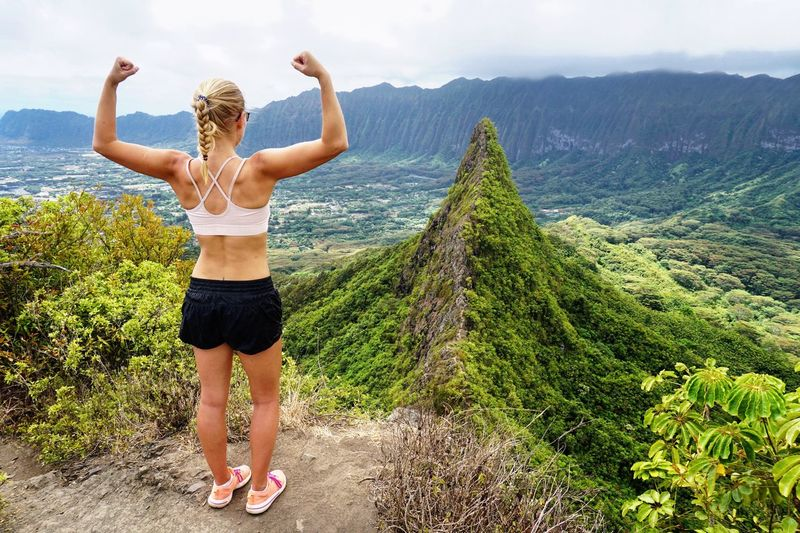 Achievement hiking in Hawaii Lifestyles Real People Young Women Leisure Activity Beauty In Nature Beautiful Woman Blond Hair Achievement Strong Woman Strong Fitness Training Fit Woman Hiking Hawaii Mountain Range Pali Lookout On Top Of The World Be. Ready.