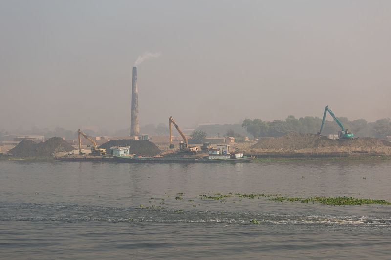 View of factory by sea against sky
