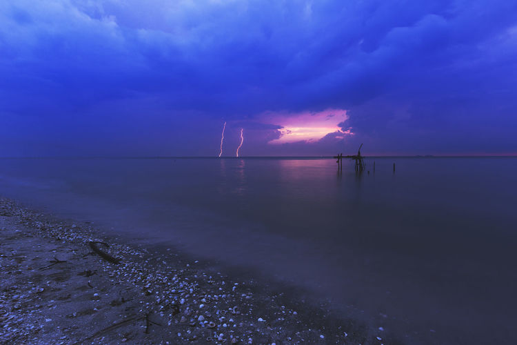 A lighting strike was captured at a beach. Beach Beauty In Nature Cloud - Sky Day Horizon Over Water Idyllic Nature No People Outdoors Scenics Sea Sky Sky, Storm, Stormy, Light, Lightning, Nature, Power, Strike, Dark, Blue, Weather, Thunderstorm, Striking, Thunder, Dramatic, Bright, Cloud, Electric, Energy, Danger, Bolt, Electricity, Rain, Night, Background, Flash, Thunderbolt, Extreme, Shock, Overcast, Sunset Tranquil Scene Tranquility Water