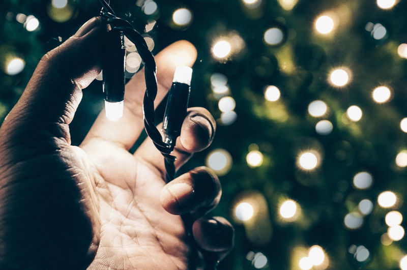 Close-Up Of Hand Holding Illuminated Christmas Tree At Night