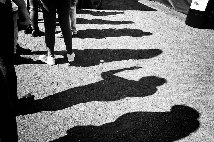 Shadow of people standing in queue