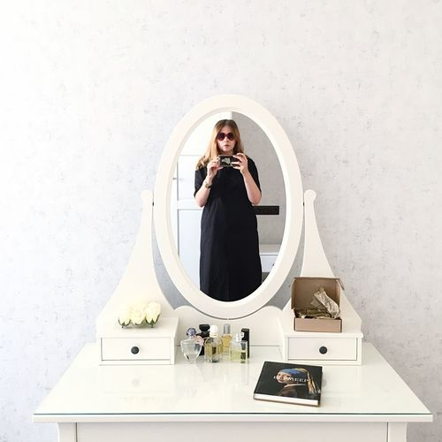Young Woman Taking Selfie With Smart Phone Reflecting On Mirror At Home