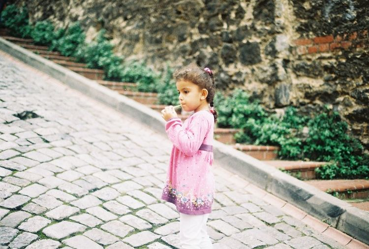 Cute girl looking away while standing on footpath