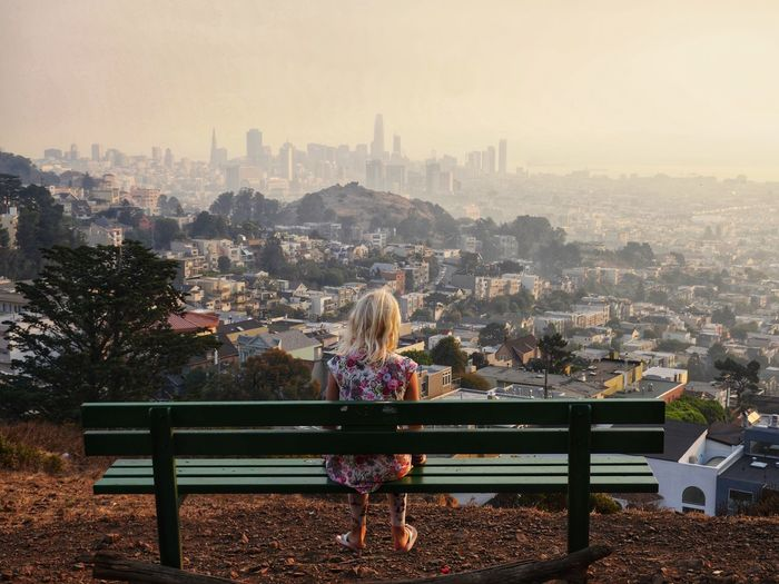 Rear view of girl looking at cityscape while sitting on bench against clear sky