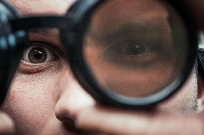 Close-up portrait of man looking through eye test equipment