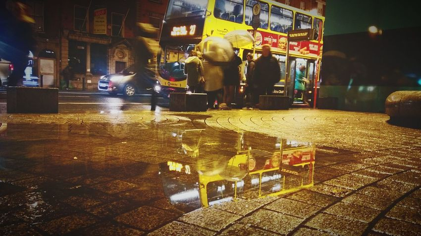 Illuminated Outdoors People Building Exterior Water Architecture Reflection Night Adult City Wet Public Transportation Public Transport Public Space Busstop Bus City Bus Rainy Night Dublin Bus