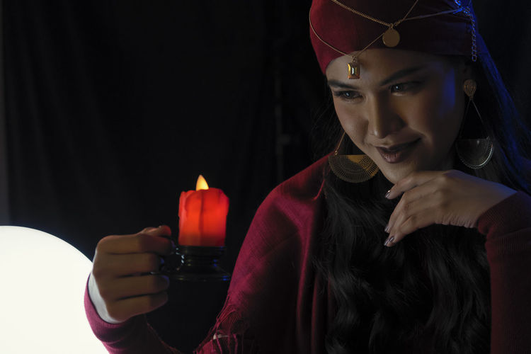 Female fortune teller with burning candle against black background