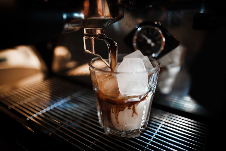 Close-up of coffee pouring in drink glass at cafe