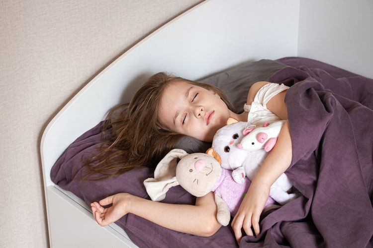 Portrait of girl lying down on bed at home