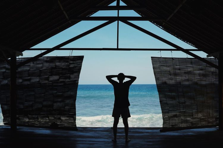 Silhouette man standing in hut at sea shore against sky