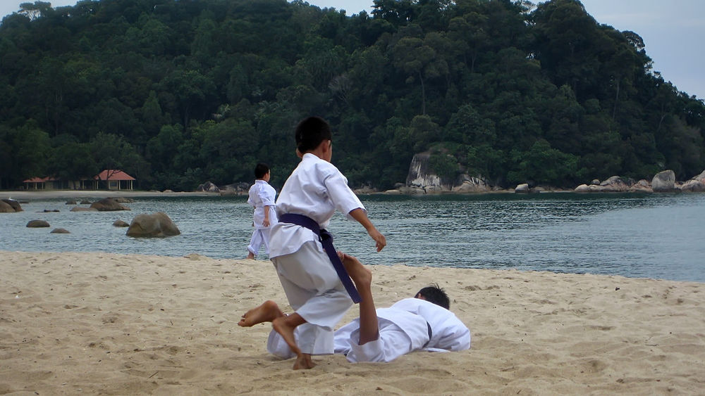a group of school children are practicing karate on the beach Beach Combat Group Of People Instructor Island Karate Kick Martial Arts Children Practice Punch Sand Trening
