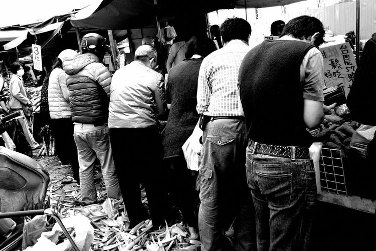 Rear view of people standing in market