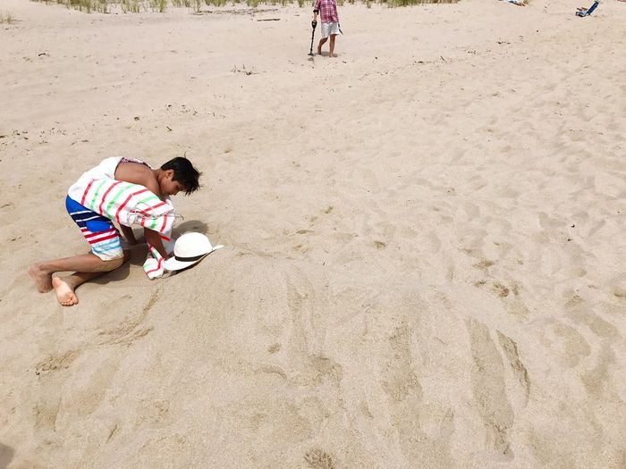 Boy On A Beach Buried In Sand Sand High Angle View Beach Childhood One Person Full Length One Man Only People Only Men Day Adult Playing Vacations Outdoors Men Nature Adults Only Buried Treasure Lifestyles Nature Sunlight Boys