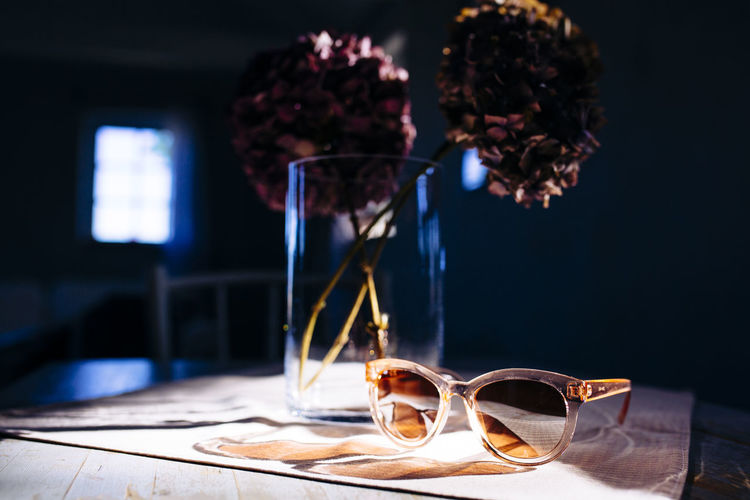 Close-up of flower vase and sunglasses on table.