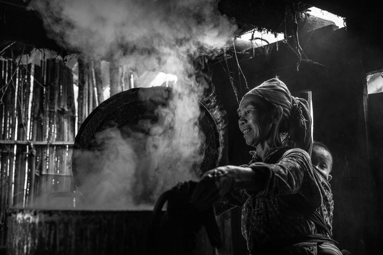 Real People Smoke - Physical Structure Lifestyles People Side View Adult Women Heat - Temperature Burning Motion Night Smoke Waist Up Fire Young Adult Standing Two People Child Kitchen Cooking Smoke North Vietnam Rural Housewife Housewife Life Baby Roof Rooftop