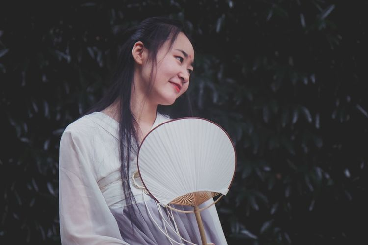 Smiling woman with hand fan standing against plants