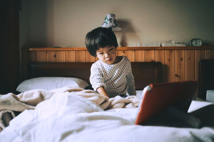 Boy watching video over digital tablet while sitting on bed at home