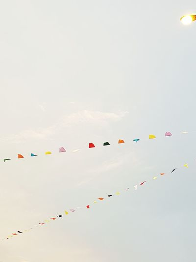 Low angle view of colorful buntings hanging against sky