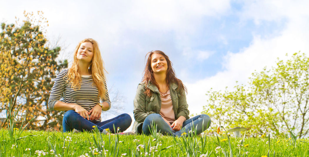 Tow girls sitting on a meadow in spring Baden-Württemberg  Females Friends Fun Happiness Happy Enjoyment Friendship Germany Grass Happiness Health Healthy Long Hair Nature Park People Portrait Puberty Relaxation Sitting Smiling Togetherness Two People Women