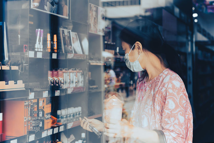 Woman in protective mask shopping in beauty and make up store shot through window.