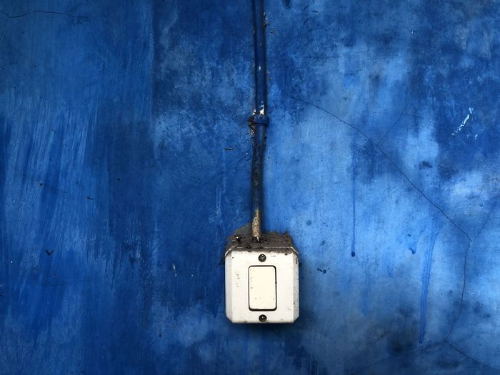Close-up of electric lamp on blue wall