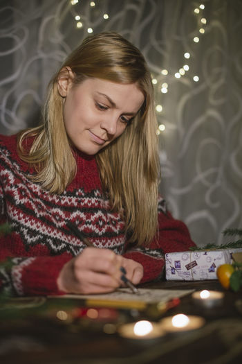 Young blonde woman writing on the postcard at home Christmas Christmas Decoration Celebration New Year Indoors  Wood Table Decoration Preparation  Wax Postcard Home Hobby Caucasian Icelandic Blonde DIY Craft Lifestyle Domestic Real People Lifestyles Women One Person Portrait Holiday Moments