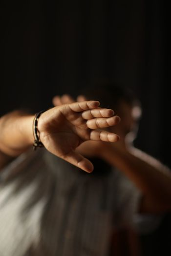 Low angle view of man showing stop gesture