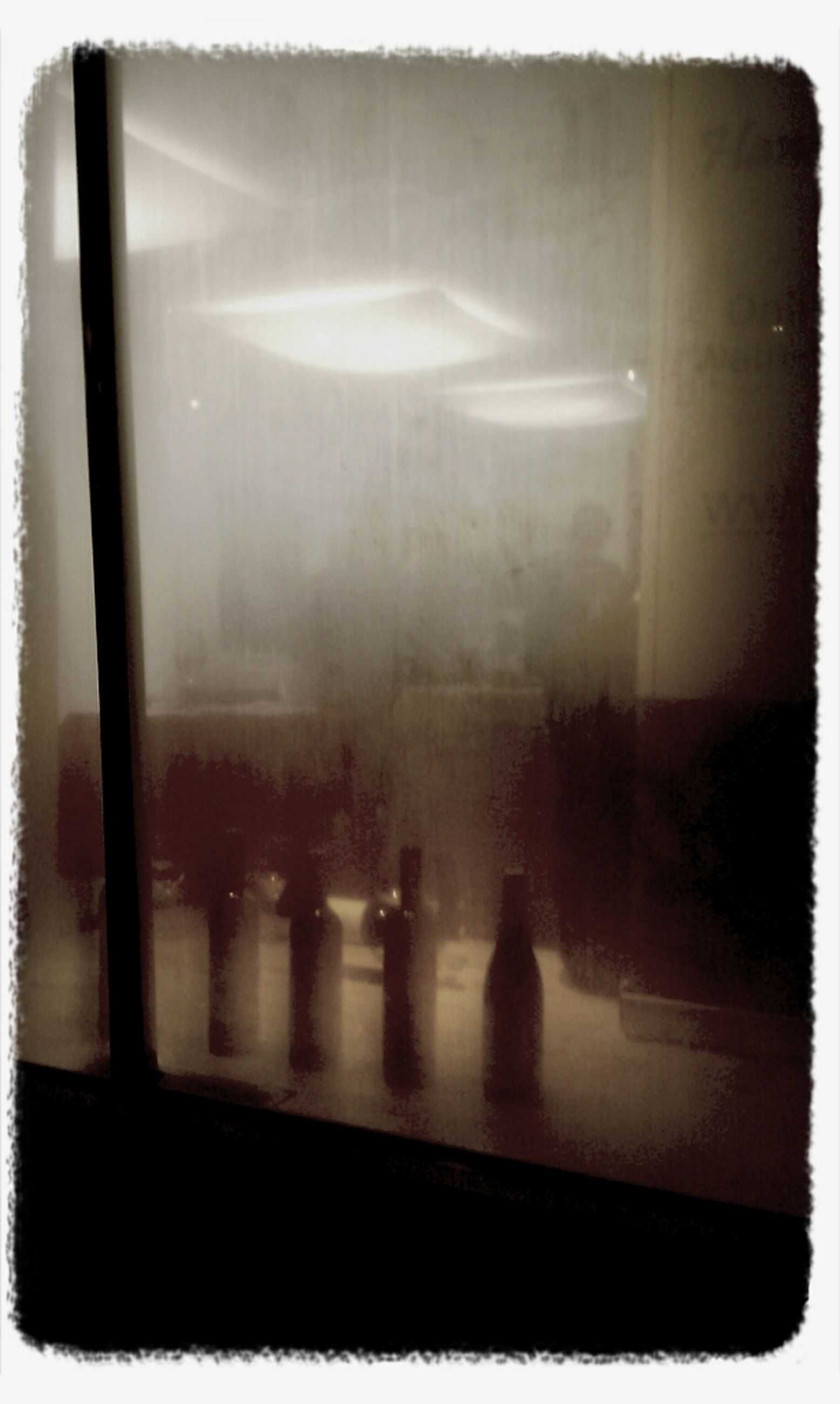 transfer print, indoors, window, glass - material, transparent, auto post production filter, glass, reflection, water, looking through window, vehicle interior, wet, close-up, transportation, rain, no people, illuminated, mode of transport, day, drop