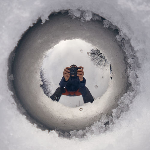 Reflection of man photographing in snow