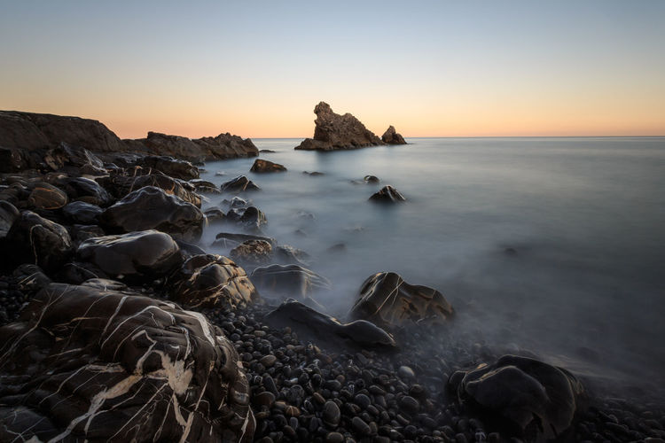 Sunset Landscape Travel Destinations Morning Scenics Dawn Outdoors Silhouette Nature Fog Tranquility Sky Sea No People Beach Beauty In Nature Horizon Over Water Winter Cold Temperature Horizon Rocks Stones Long Exposure Italy🇮🇹 Beauty In Nature