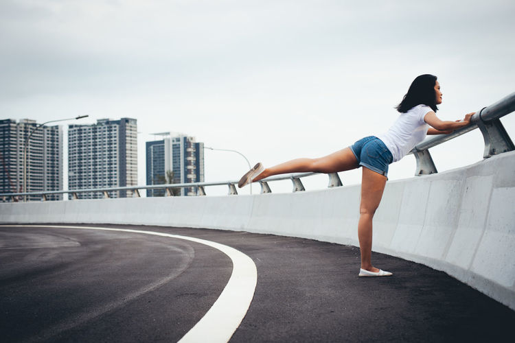 Full Length Side View Of Woman Exercising By Railing On Bridge In City Against Sky