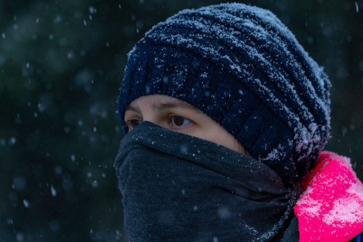 Close-up of woman covering face with textile during snowfall