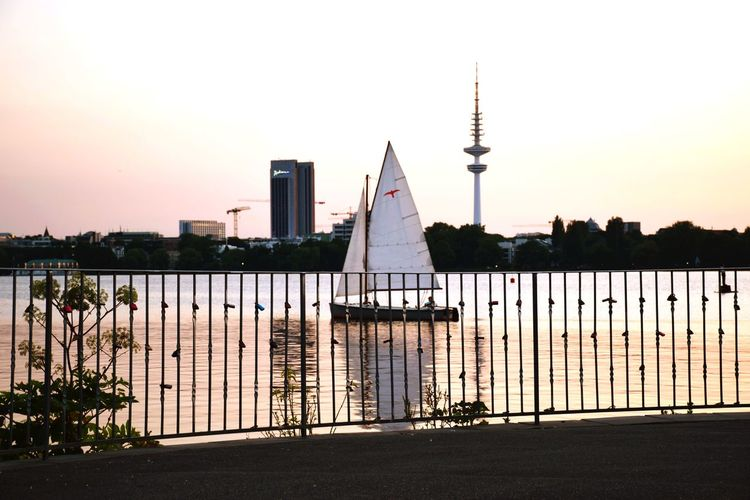 Nature Railing By The Water Reflections In The Water Sunset Silhouettes Beauty In Nature Sunlight Day Outdoors Sailing Boat Focus On Foreground Waterfront City Urban Skyline Cityscape Skyscraper Tree Water Sky Architecture Tower Communications Tower Skyline Tall - High Television Tower
