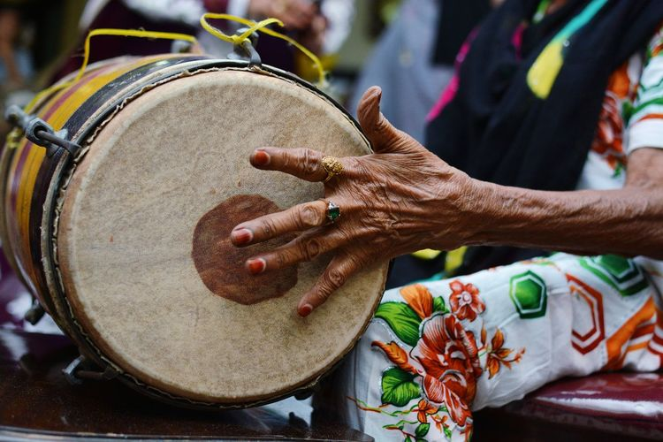 Old Indian lady playing the traditional Indian drum called Dholak Dhol Drums Lady Old Music Human Hand Men Occupation Arts Culture And Entertainment Close-up Musical Instrument String Musical Instrument Musician