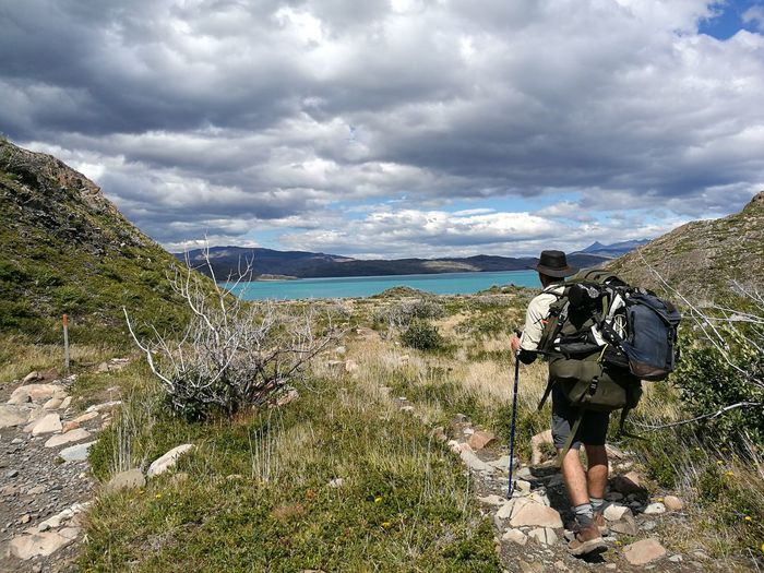 Rear view of hiker walking on field by lake pehoe against cloudy sky at torres del paine national park