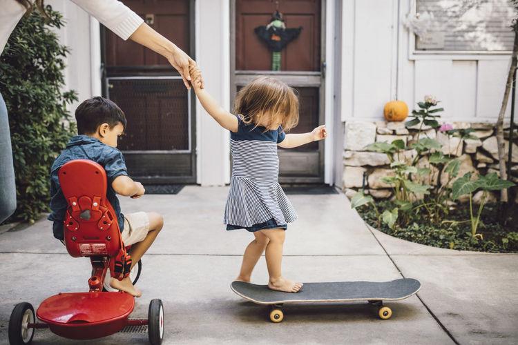 Full length of children playing in shopping cart