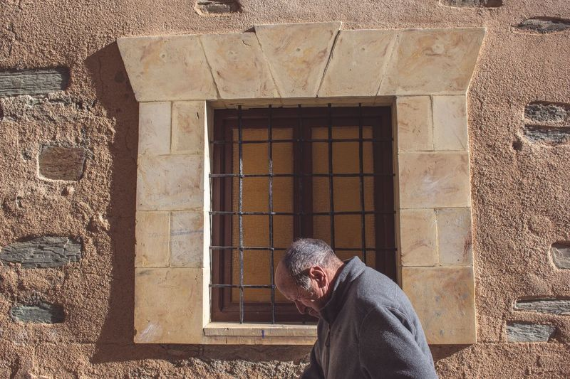 Man standing against window of building