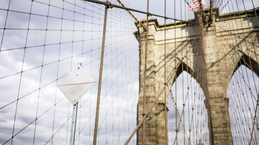 Low Angle View Of Blank Road Sign And Cables At Brooklyn Bridge Against Sky