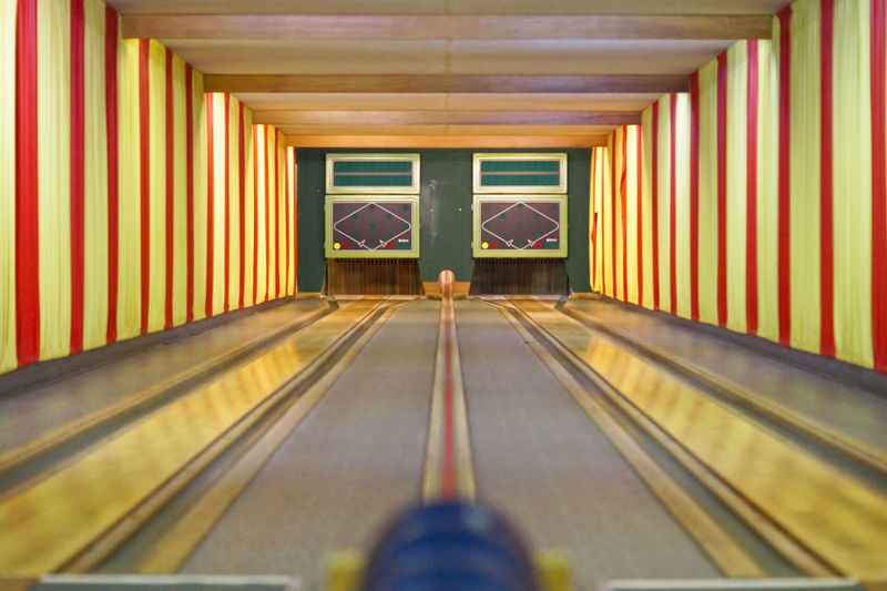 Arcade Architectural Column Architecture Bowling Bowling Alley Bowlingnight Building Built Structure Ceiling Day Diminishing Perspective Direction Empty Flooring Glass - Material Illuminated Indoors  Multi Colored Ninepins No People Pattern Skittles Striped The Way Forward Transportation Yellow