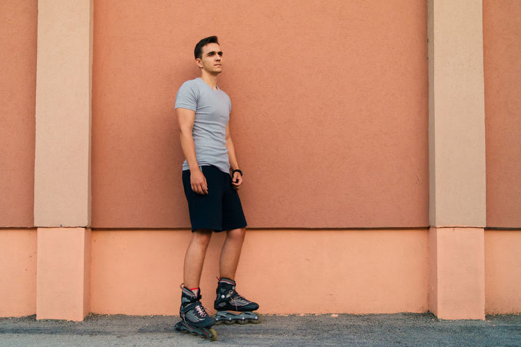 Full length of man with roller skates leaning on wall