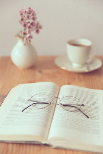 High Angle View Of Eyeglasses On Book With Tea Cup On Table