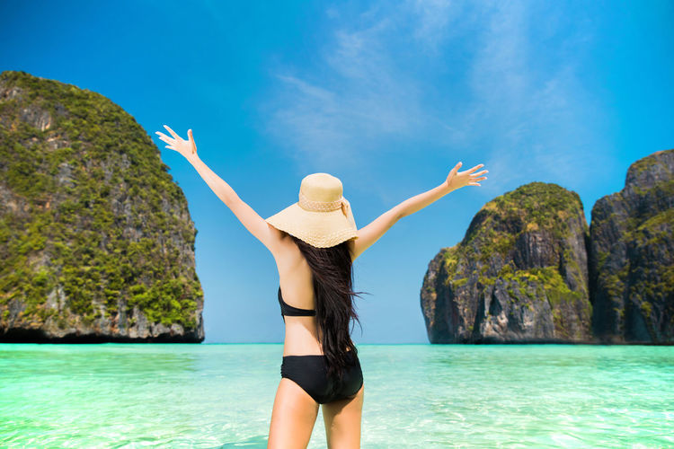Arms Raised Beauty In Nature Clothing Day Hairstyle Hat Holiday Human Arm Leisure Activity Lifestyles Limb Nature One Person Outdoors Real People Rock Sea Sky Standing Trip Vacations Water Women