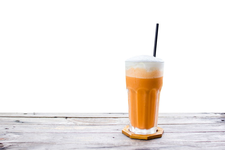 Thai tea iced frappe with cream on wood table on white background. Close-up Day Drink Drinking Glass Drinking Straw Food Food And Drink Freshness Frothy Drink Healthy Eating No People Outdoors Refreshment Studio Shot Table White Background Wood - Material