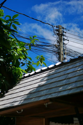 Low angle view of electricity pylon by building against sky