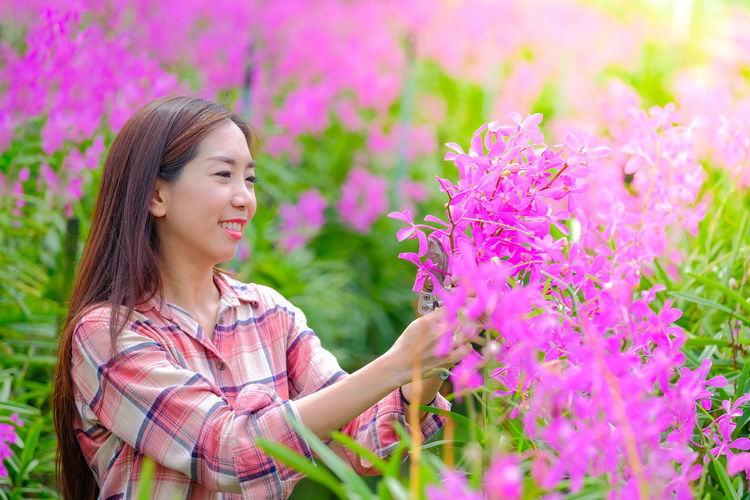 Portrait of a smiling young woman against purple flowering plants