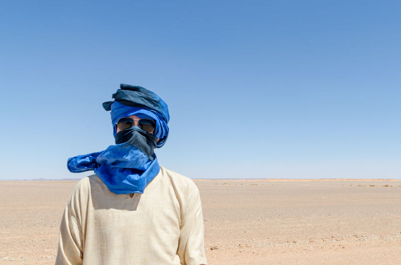 Man with headscarf standing in desert against clear blue sky