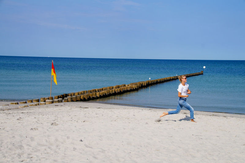 Full length of woman running on beach against sky